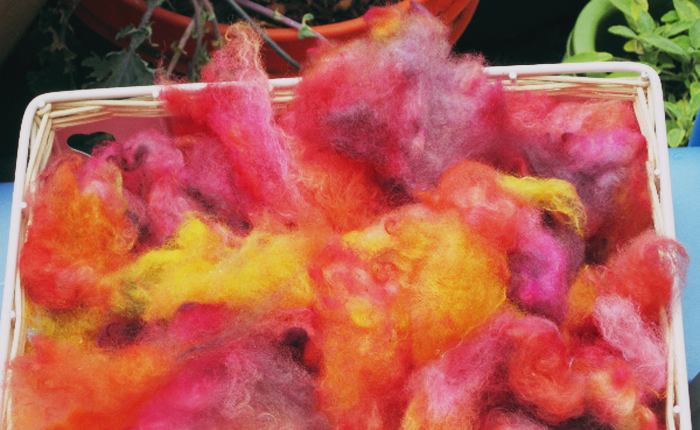 A basket containing dyed fleece in bright colors.
