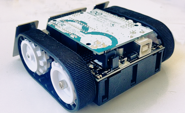 Picture of a small robot with rubber tank tread wheels and a circuit board on top.