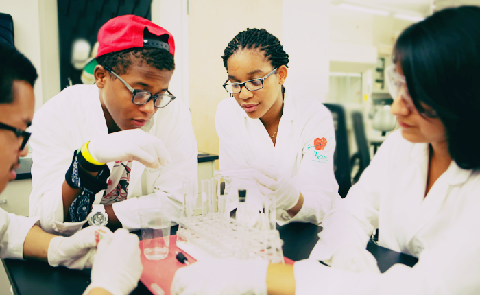 Four LPFI students sit around a square black table covered with science equipment, including a holder for vials and a glass of water. The students are all wearing white lab coats and white gloves, and looking intently at the materials.