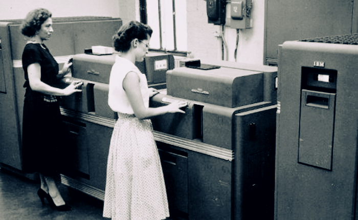 A vintage black and white photograph of two women, backs turned to the camera, working at an IBM punch card computer about the size of two large xerox machines.