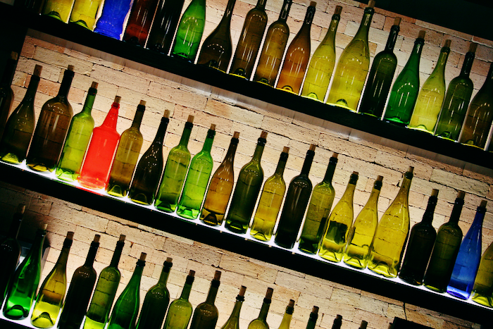 A bunch of empty wine bottles on shelves with a brick background.