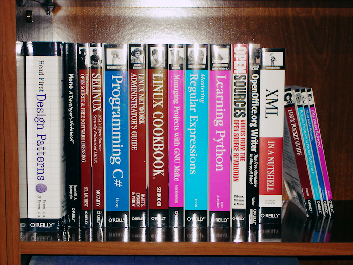 A bookshelf full of programming books, including Linux Cookbook, Mastering Regular Expressions, Head First Design Patterns and more.