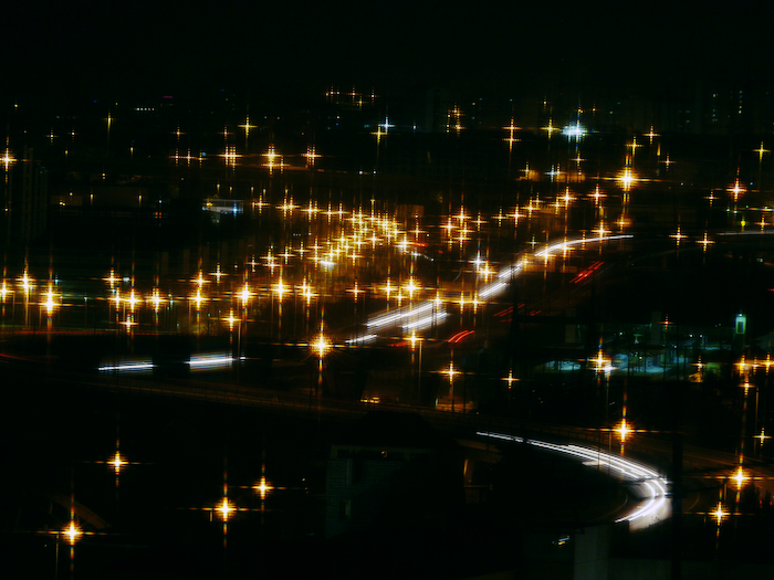 Blurry image of cars at night.