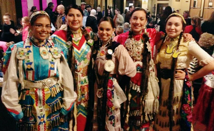 Five Indigenous women standing next to each other smiling. They are from tribes across Montana and wearing powwow regalia called jingle dresses. All have two braids, and beadwork in the form of hair ties, leggings, moccasins, neckties, belts, and earrings.