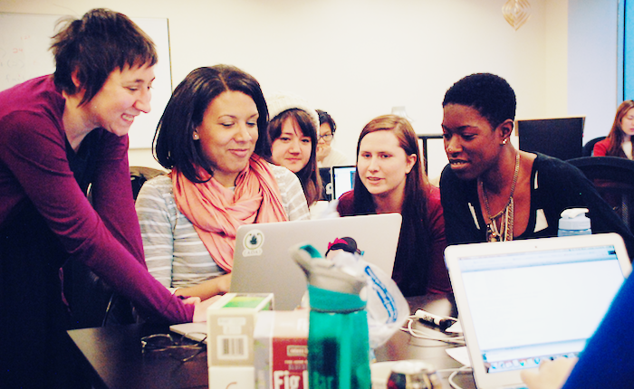 Group of women around a computer.