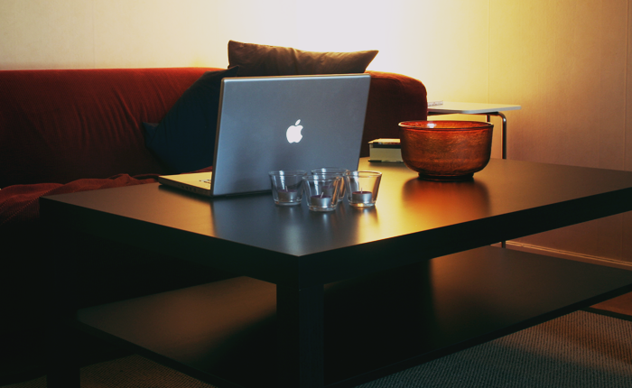 Photo of a couch and coffeetable workspace, with a laptop open.