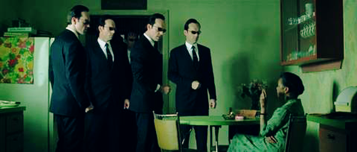 The Oracle character in the matrix sits at a table in a kitchen. The Smiths, a group of men in suits, stand in a group, appearing to question her.