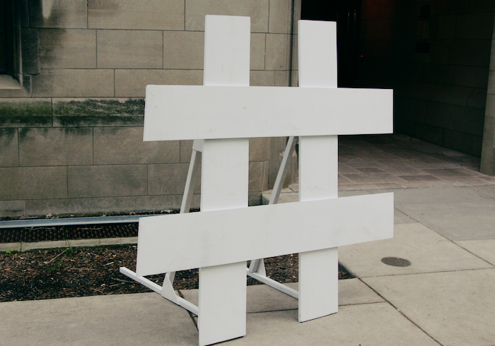 A large 3D hashtag erected by painted boards of wood against a concrete background.