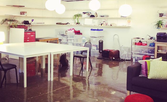 A photo of the Double Union workspace. The floors are shiny, cement and a large square white table with a few chairs is in the center of the shot. On white shelves on the walls are plants, sewing equipment, and various supplies. A red workbench and plastic tubs full of tools are lined up near the walls.