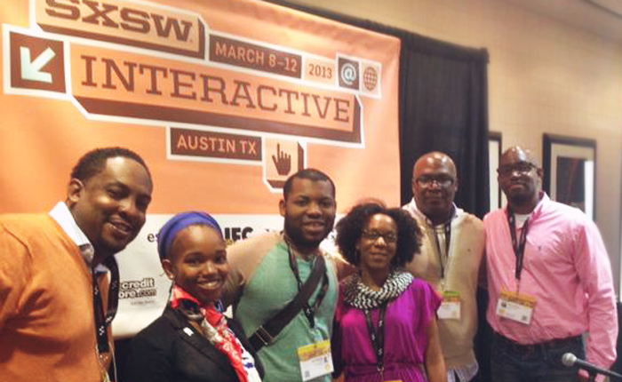 Johnson, the author, posing in the middle of a group of five other SXSW attendees. A large conference banner is behind them.