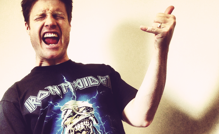 Photo of a white man in an Iron Maiden shirt playing air guitar.