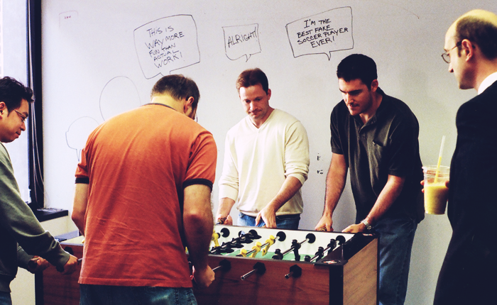 A group of five men play foosball in an office environment. In the background a whiteboard wall has speech bubbles drawn on them, one of which reads 'This is way more fun than actual work!' and appears to line up with the head of one of the foosball players.