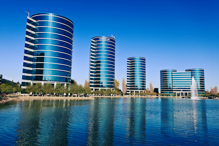Photo of the Oracle campus behind a vast blue fountain. The four office buildings are looming, reflective, futuristic, blue and cylindrical against a day sky.