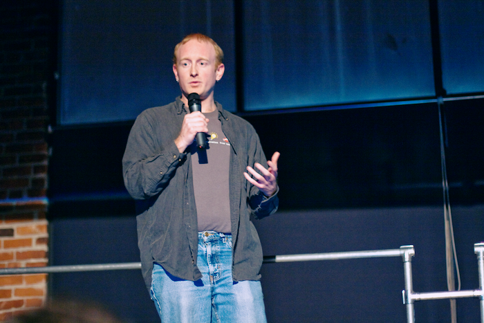 Photo of the author speaking at an event, holding a microphone and gesturing.