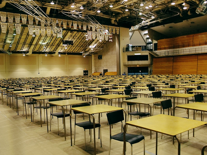 Rows and rows of desks set up in a large auditorium.