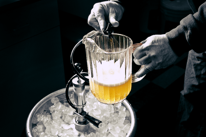 A pitcher being filled with beer from a keg.