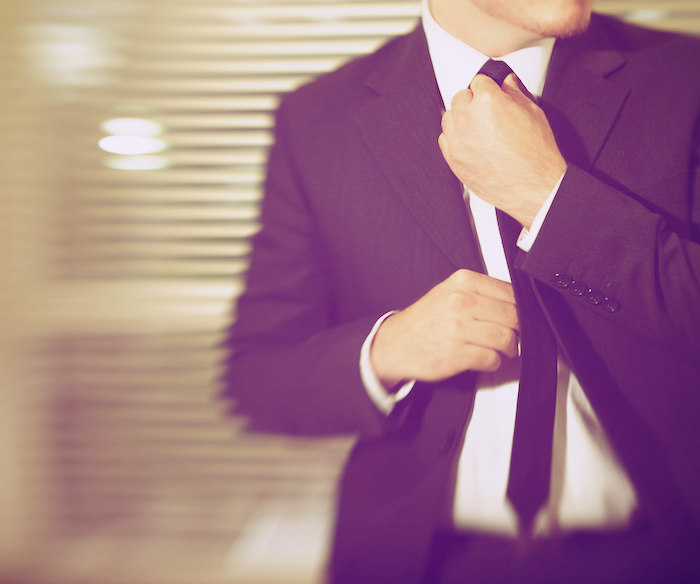A man in a business suit, adjusting his tie, his face turned from the camera.