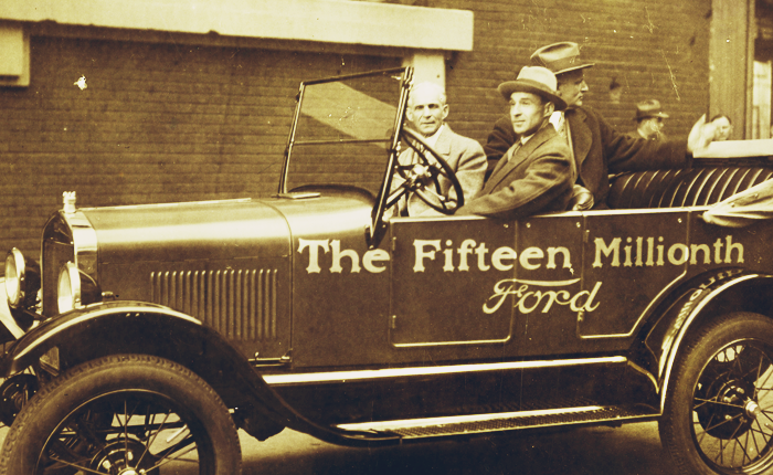 Scan of a vintage photo of Henry Ford riding in a Model-T car, which is emblazoned Fifteen Millionth Car.