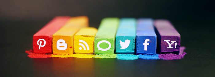 Social media logos for Pinterest, Twitter, Facebook, RSS, Blogger and others transposed on a series of rainbow-colored chalks.