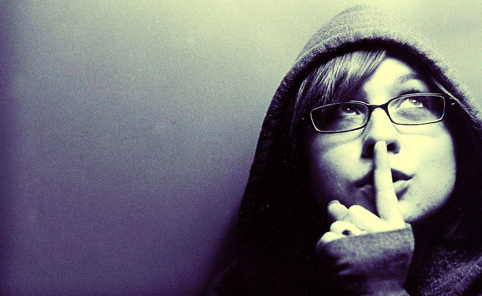 Woman with a finger over her mouth in the shhh pose.