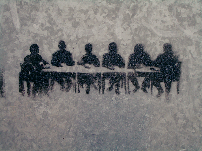 An image of six people at a meeting table, made using stencil graffiti on a galvanised steel background.