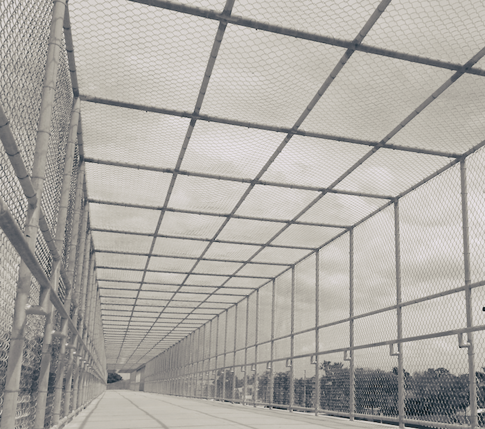 A bridge enclosed in wire fencing.