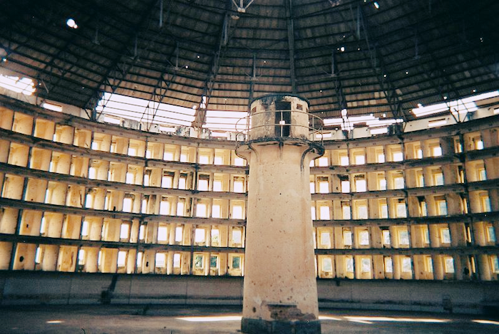 Photo of a panopticon prison with guard tower looming before dozens of cells.
