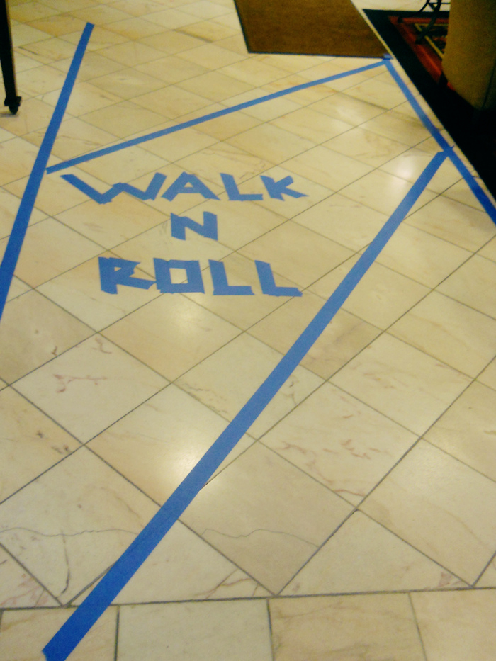 Blue tape accessibility lanes. Reads 'Walk n Roll'.