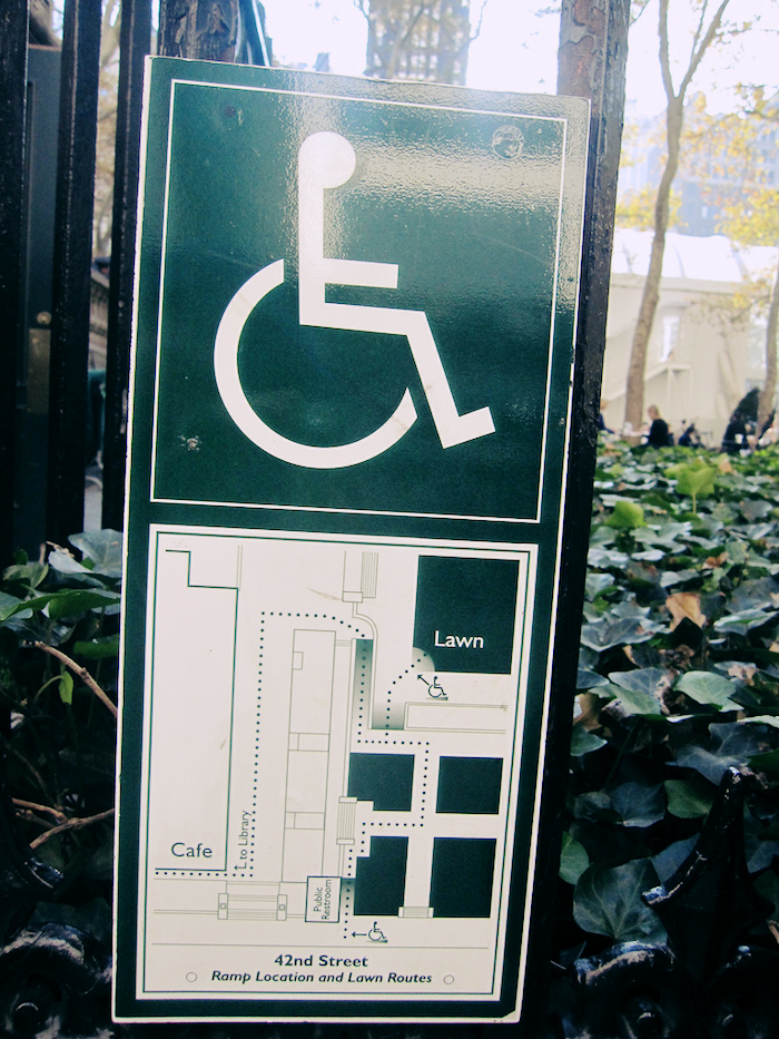 A prominent outdoor sign displaying accessibility information for a facility.