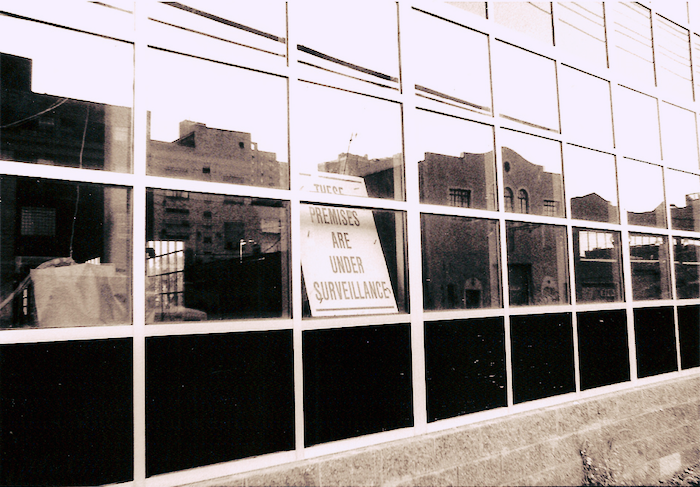 A sign in a window that reads These Premises Are Under Surveillance.