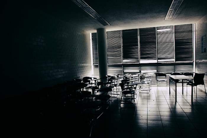 Desks in an empty classroom with the blinds closed.