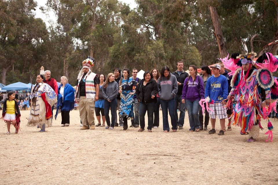 Picture from the Stanford powwow native graduating class, attendees gathered in a half-circle and flanked by trees.