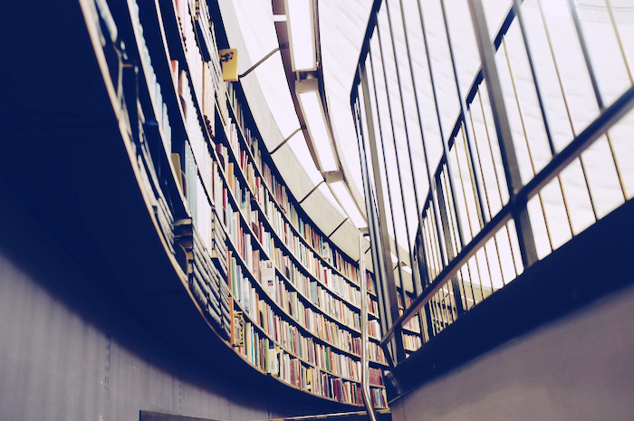 Stairs leading up to a library full of stocked bookshelves.