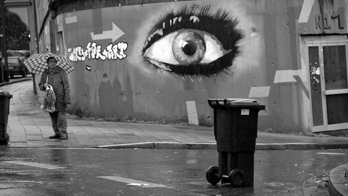 A large image of an eye painted on a wall set back from the street.