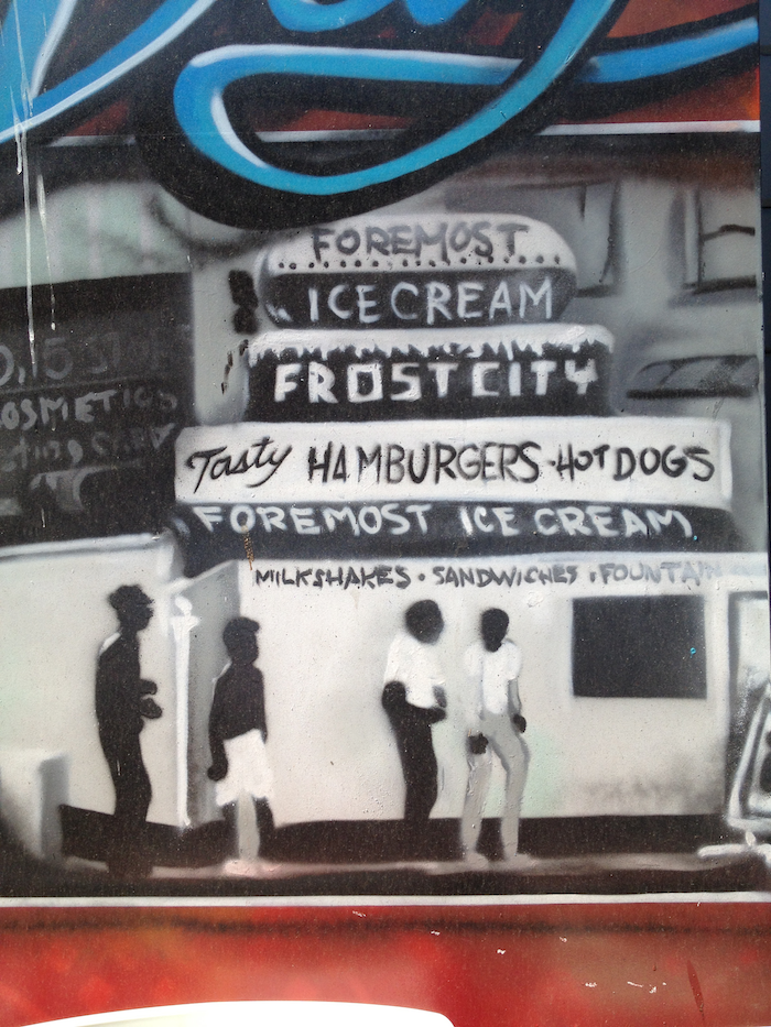 Artwork of four Black people standing outside a storefront that reads 'Foremost Ice Cream. Frost City. Tasty Hamburgers. Hot Dogs.'