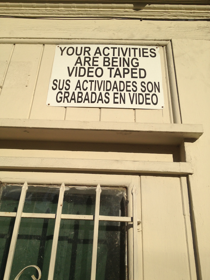 A sign on a building that reads 'Your activities are being video taped. Sus actividades son grabadas en video.