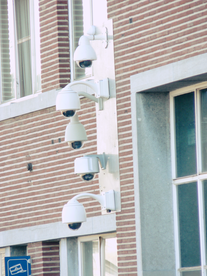 A pole with half a dozen security cameras against a brick building.