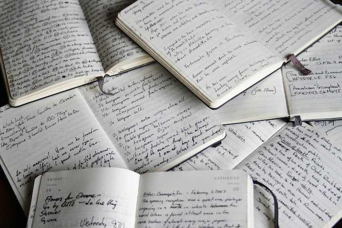 A pile of open notebooks with writing in it.