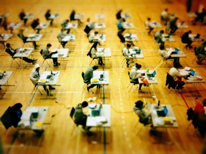 Students in rows of desks, taking a test.