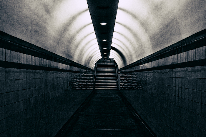 A dark tunnel with stairs leading up at the end.