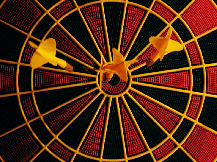 Dart board with three darts near the bullseye.