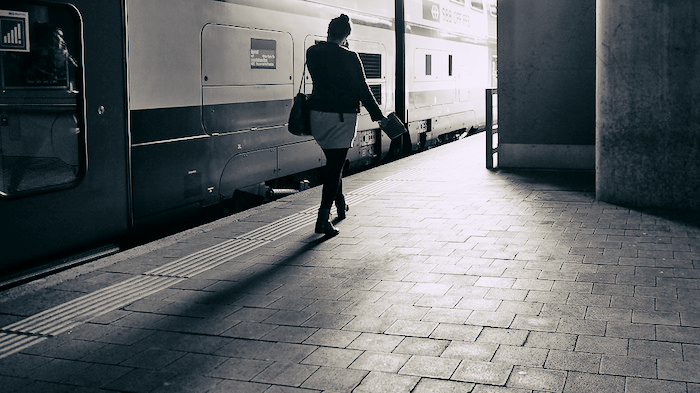 A woman walking down a train platform, the camera angle as if someone is following her.