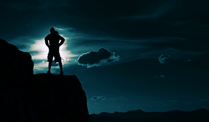 Super hero-like figure looking out over a cliff.