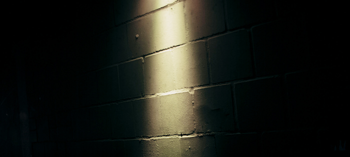 A dark wall with a sliver of light illuminating bricks.