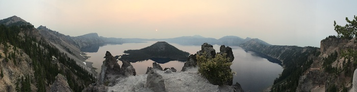Panoramic of Crater Lake, a scenic view of water, mountains, trees and hazy sun.