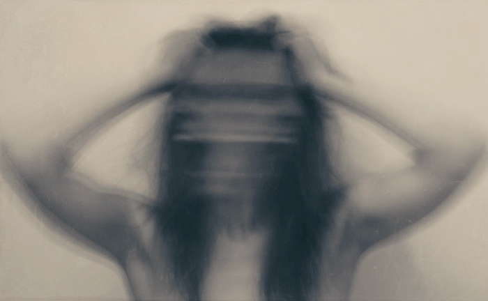 Blurry image of a person yelling and pulling their hair.