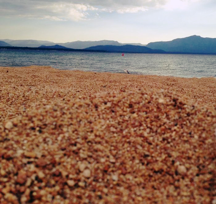 A sandy beach with water and mountains in the background.