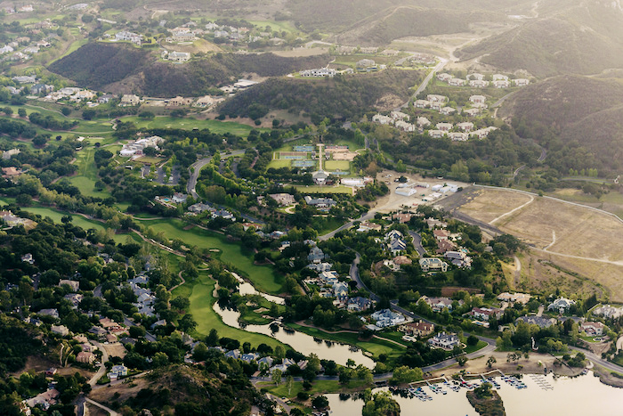 Aerial shot of a lush country club with golf courses and large houses.