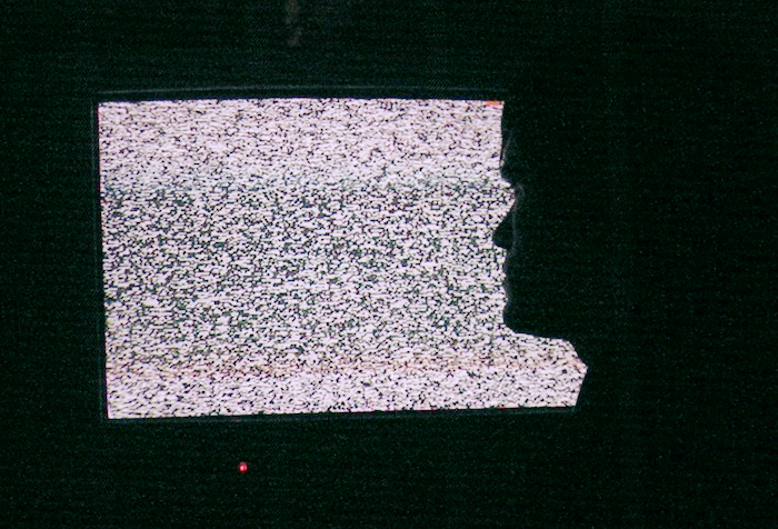 A static-filled television behind the profile of a face.