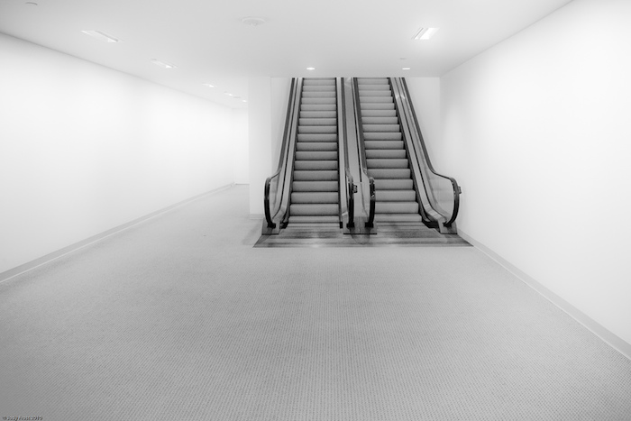 Escalators in a bright, empty room.